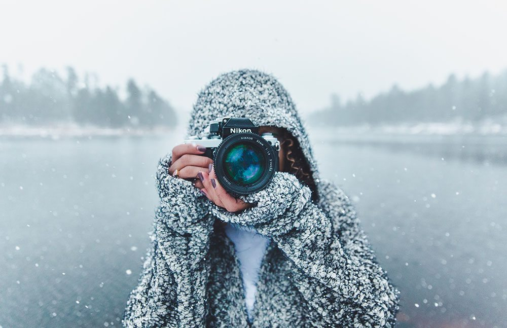Woman in the Snow taking a photo